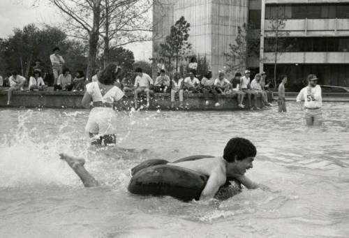 Students playing in UH's Cullen Family Plaza Fountain and Reflecting Pool. April 1987. Special Collections, University of Houston Libraries.