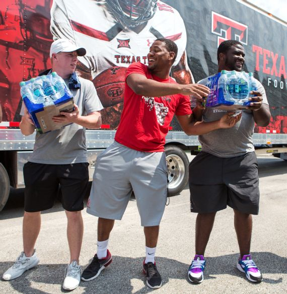 Mason McClendon, Kevrin Justice, Blake Young and Chantez Jackson pass water down an assembly line as they unload a Texas Tech truck full of donated supplies in Houston. Photo: Michael Starghill, Jr. for ESPN